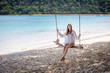 Girl sitting on the swing on the tropical beach