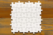 Puzzle Background. White Pieces On Wooden Table. Partially Completed Square Shaped Puzzle Pieces.