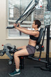 Portrait of beautiful middle aged white caucasian brunette woman with short hair doing exercises in gym