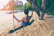 Young asian woman traveler in bikini relaxing and enjoying on wooden swing under tree and looking destinations beach, Pak Bea island, Andaman sea, Krabi Province near Phuket Thailand.
