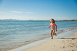 Cute happy little girl running along the beach in swimming suit, jumping over waves. Beautiful summer sunny day, blue sea, turquoise water, picturesque landscape. Majorca, Spain
