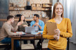 So pretty. Young beautiful positive woman standing with a folder in her hands while her calm pleasant skilled coworkers sitting at the table and talking