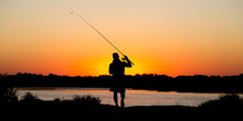 Silhouette Of A Man With A Fishing Rod At Sunset