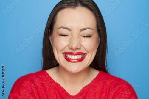 Fotografie, Obraz  beautiful ashamed woman in a red blouse on a blue background