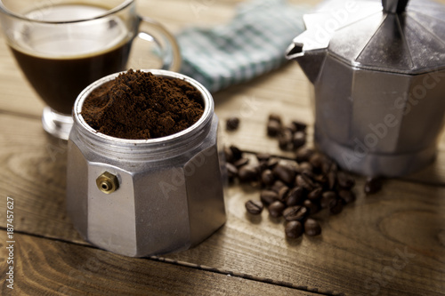 Fototapeta  Italian coffee maker with napkin and cup of coffee on table