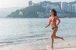 Sporty young woman in bikini running along the beach with bright sunlight and mountainous resort city in background
