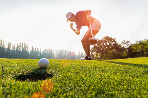 Deurstickers Golf Asian woman golfer action to win after long putting golf ball on the green golf, sunset time, copy space. Healthy Concept
