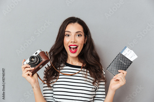 Portrait of an excited woman holding vintage camera