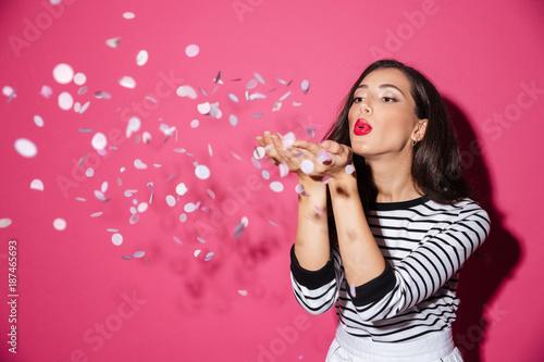 Fotografie, Obraz Portrait of a pretty woman blowing confetti