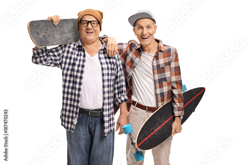 Two elderly skaters with longboards looking at the camera and smiling