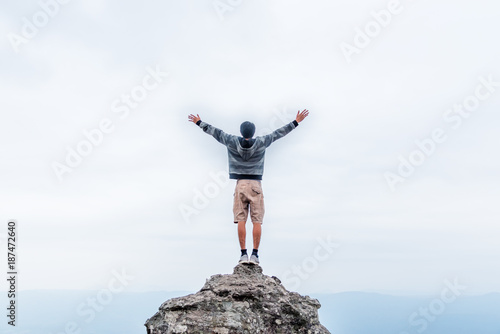 Photo  Young man stay on rock and spreading hand for enjoying sky view.