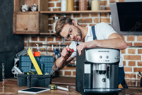 Fotografie, Obraz professional young repairman in eyeglasses fixing coffee machine