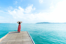 Summer Day. Smiling Women Relax And Wearing Red Dress Fashion Standing On The Wooden Bridge Over The Sea, Blue Sky Background. Travel And Vacation. Freedom Concept