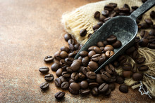 Roasted Coffee Beans And Spoon On Brown Rustic Background.Copyspace