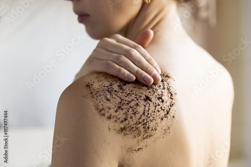 Fotografie, Obraz Beauty, spa and healthy skin concept - woman cleans skin of the body with coffee scrub in bathroom
