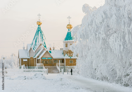Photo A small wooden Orthodox church is covered with snow in a snow-covered forest