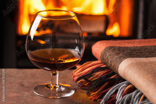 Foto op Plexiglas Alcohol a glass of cognac in front of fireplace