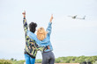 Women looking on flying plane