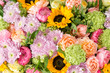 Leinwanddruck Bild - beautiful bouquet of mixed flowers in a vase on wooden table. the work of the florist at a flower shop. a bright mix of sunflowers, chrysanthemums and roses. background on full screen