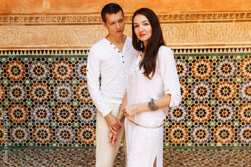 a2d818501ce0 Dreamy couple dressed in white closes walks around African city Marrakesh in  a sunny evening