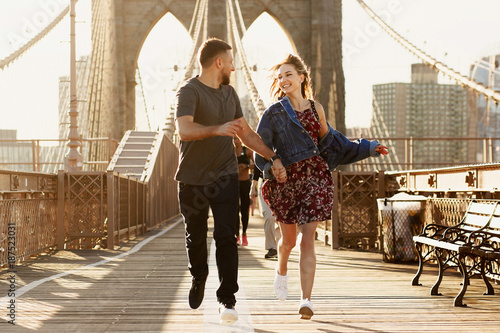 Photo  Beautiful young man and woman pose on the Brooklyn Bridge in the rays of morning