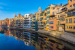 Colorful river-front houses lining the Onyar river, mostly built on top of old medieval defense walls, Girona, Catalonia, Spain