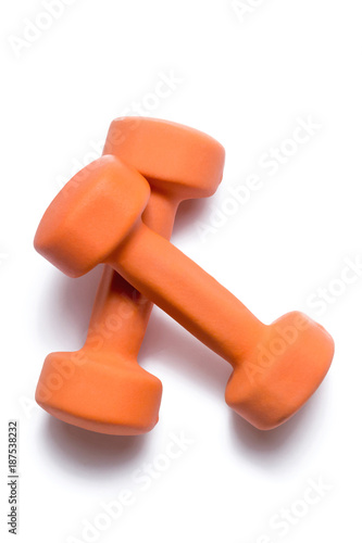 Fotografía  Two orange dumbbells lie on top of each other on a white background