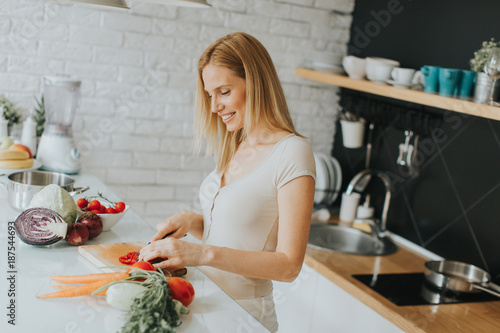 Foto op Plexiglas Koken Pretty young woman preparing healthy meal in the modern kitchen