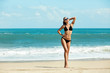 Close-up beautiful luxury slim and tanned girl in a black bikini on the beach the ocean. Outdoor summer lifestyle image of young pretty woman outfit and sunglasses, fun ,joy, emotions.