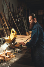 Carpenters Working In Workshop/sawmil With Wood On Circular Saw.