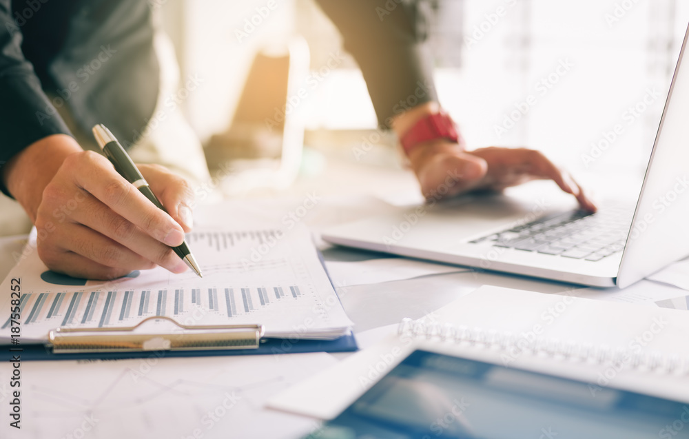 Fototapeta Businessman holding pen and pointing paper chart summary analyzing annual business report with using laptop at room office desk.
