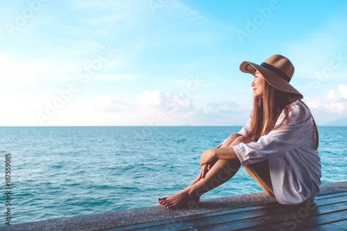 Foto auf AluDibond Licht blau Portrait image of a happy beautiful asian woman on white dress sitting on wooden balcony by the sea with clear blue sky background