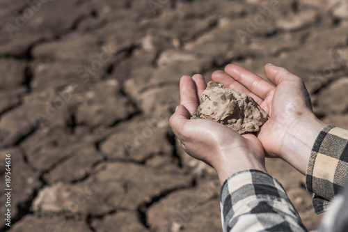 Hand woman holds a dry clay dirt with despair on dry soil