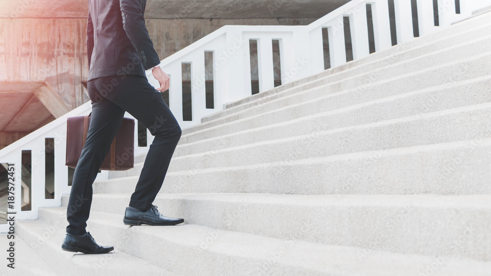 Fototapeta Young Smart Businessman holding suitcase and walking up the stairs.Concept of success business step.