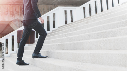 Young Smart Businessman holding suitcase and walking up the stairs Fototapeta