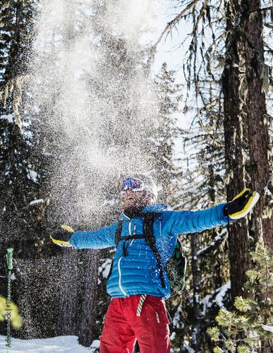 Portrait of skier, celebrating in snow