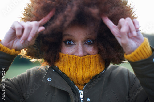 Portrait of young woman outdoors, wrapped up warm