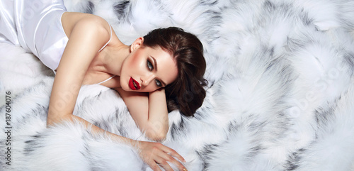 Young beautiful attractive girl in a white silk dress lies on a white fluffy ...