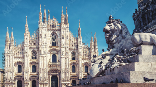 Fotografia Milan Cathedral and monument with lion statue under blue sky, Italy