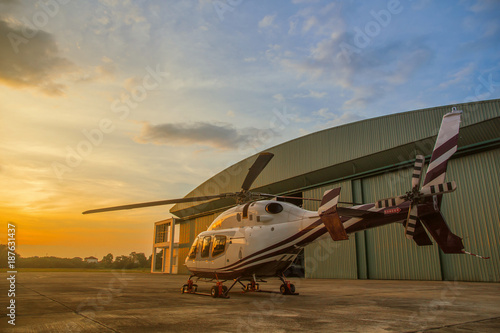 Fotobehang Helicopter silhouette of helicopter in the parking lot or runway with sunrise background,twilight helicopter on the helipad