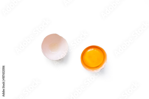 fresh brown organic chicken egg broken with yolk and egg white isolated on white background. Horizontal composition. Top view