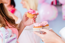 Expecting Mother Eating Pink Cupcake On Baby Shower Party