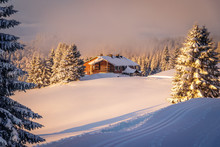A Black Forest Mountain Lodge Warmed Up By The Early Morning Sun Rays. The Cross Country Ski Track Has Been Freshly Prepared And The Fir Trees Are Covered With Snow After The Storm The Day Before.