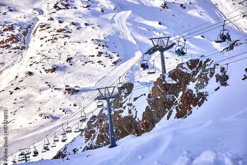 Skiers on the skilift, skiers on slope in ski resort Italian Alps in sunny day on glacier Val Senales, Italy #187676833