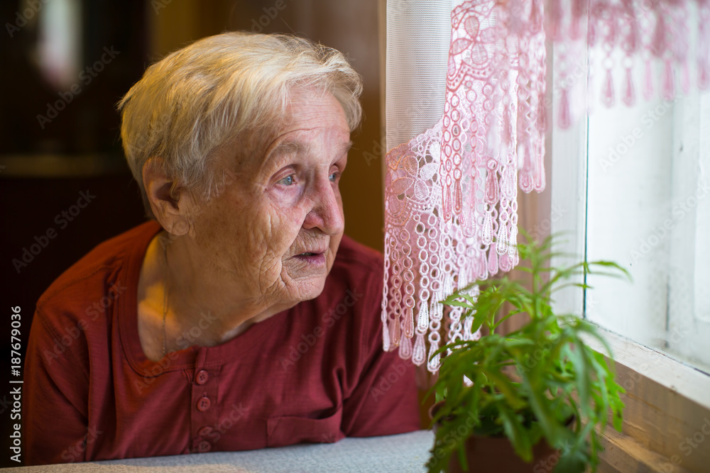 Fototapeta Older woman with longing looks out the window.
