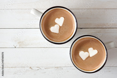 Foto op Plexiglas Chocolade Two cups of hot chocolate with heart shaped marshmallows over a white wood background