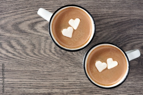 Foto op Plexiglas Chocolade Two cups of hot chocolate with heart shaped marshmallows over a wooden background