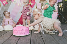 Baby Girls With Birthday Cakes On Floorboard At Party