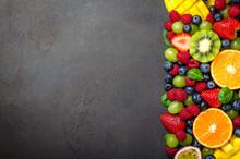 Various Fresh Fruits: Strawberry, Raspberry, Blueberry, Tangerine, Grape, Mango, Spinach On A Dark Black Stone Background. Copy Space, Top View, Horizontal Image