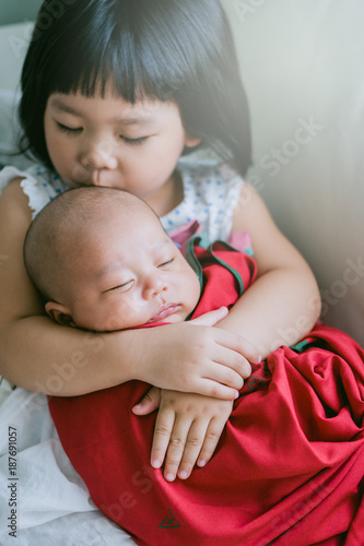f18660c72771 Little sister hugging her newborn brother.Toddler kid meeting new ...